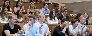 Students clapping in an auditorium