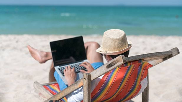Man with laptop resting in a deck chair