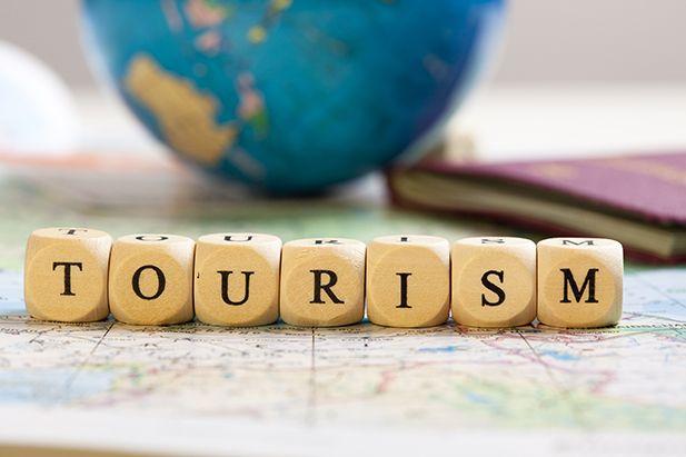 Træklodser med ordet Tourism og en globus i baggrunden