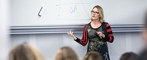 Underviser forklarer studerende en teori