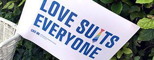 """Flag with the text """"Love suits everyone"""""""