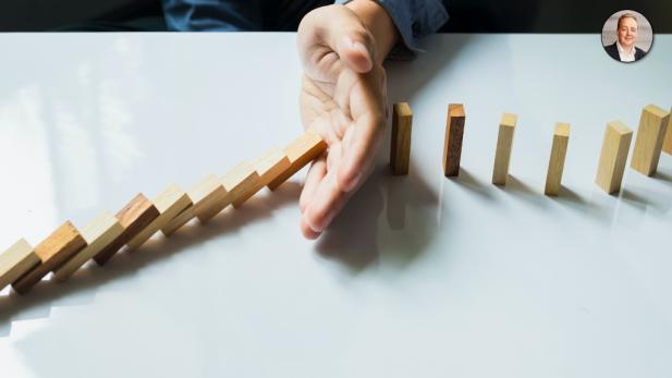 Hånd skubber til dominobrikker, som vælter på stribe
