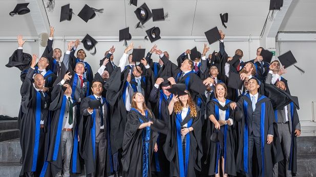 CBS Blue MBA Graduation 2019 caps in air